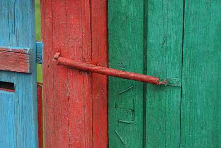 red metal spring closer on green wooden fence boards and doors on the street