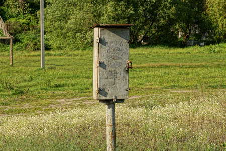 gray iron closed box for electricity stands in a field among green grass