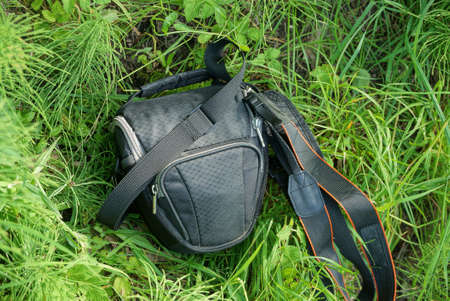 one black closed bag made of fabric lies in the green grass in nature