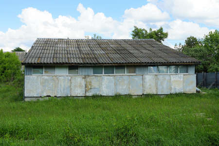 one old gray rural barn under a slate roof in green grass against the sky and clouds