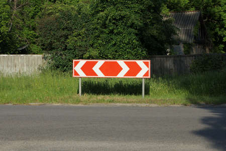 one road sign turning direction with red arrows in the green grass by the asphalt road 写真素材