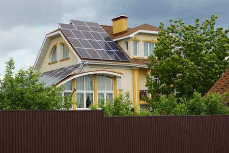 solar panels on the roof of a large private house with windows in green vegetation behind a brown fence against a gray sky