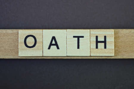 gray word oath made of wooden square letters on brown background