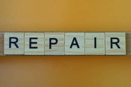 word repair made of wooden square letters on brown table