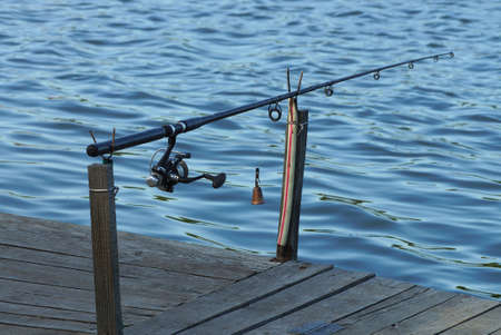 one long fishing rod with a reel on the gray wooden planks of the bridge near the blue water of the pond