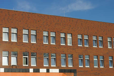 a large brown brick wall of a building with a row of windows against a blue sky