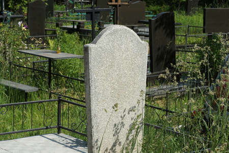 one old gray marble monument overgrown with green grass and vegetation in the cemetery 写真素材