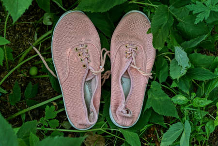 two pink female shoes made of fabric stand among the green leaves of plants in nature 写真素材