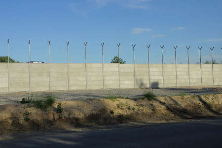 long gray concrete wall of a fence in the street with a row of lanterns against a blue sky