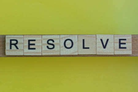 gray word resolve in small square wooden letters with black font on a yellow background