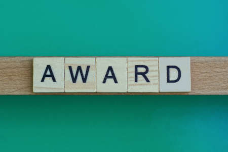 gray word award made of wooden square letters on green background
