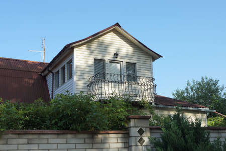 one brown iron balcony in the white attic of a private house with a brown roof overgrown with green vegetation against a blue sky 報道画像