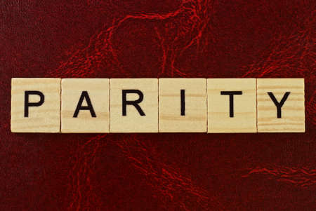 text the word parity from brown wooden small letters with black font on an red table 写真素材