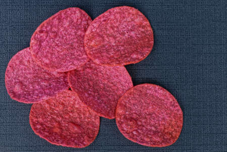 food from a pile of red dry chips lies on a black table 写真素材
