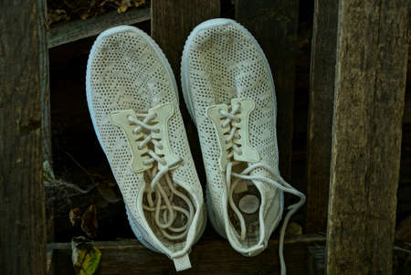 two white shoes made of fabric stand on brown wooden planks wall outdoors