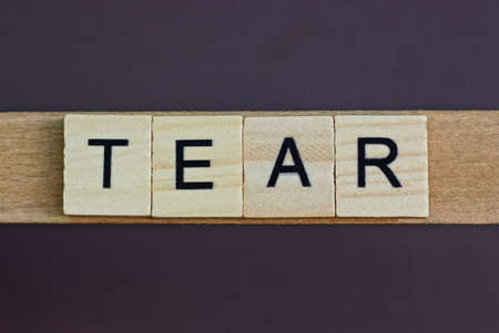 gray word tear made of wooden square letters on brown background