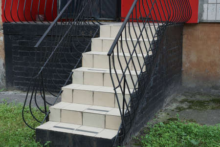 staircase of gray steps and black wrought iron handrails outside in green grass near the brick wall of the building 写真素材