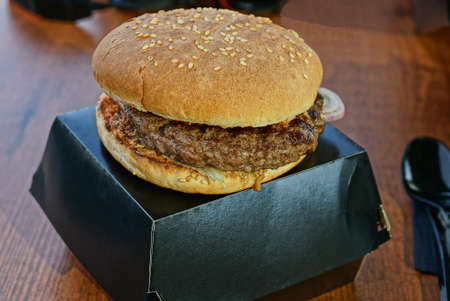 food from one large cheeseburger lies on a black paper box