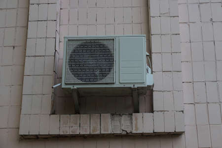 one large gray air conditioner hanging on a brown building wall outside