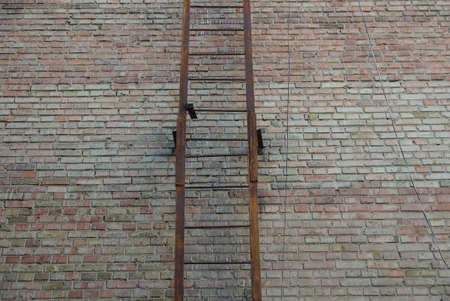 part of an old iron fire ladder in rust on a brown brick wall of a building on the street