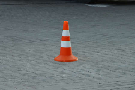 one striped plastic cone barrier stands on a gray sidewalk in the street