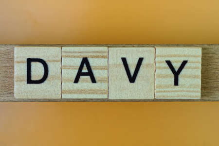 gray word davy made of wooden square letters on brown background