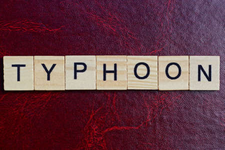 Word typhoon from gray wooden small letters with black font on an red table