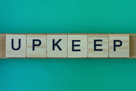 gray word upkeep made of wooden square letters on green background