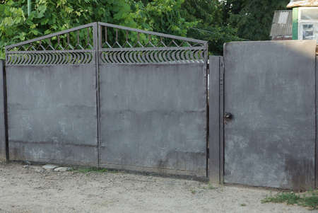 gray old iron gate and closed door on a rural street 写真素材