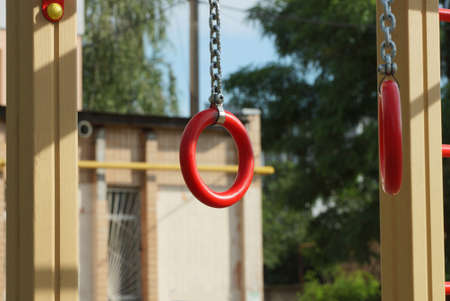 two red sports rings with gray iron chains on an outdoor sports ground 写真素材