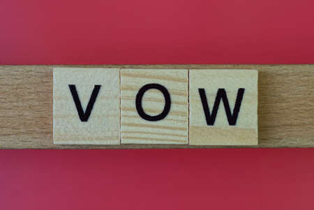 text the word vow from gray wooden small letters with black font on an red table