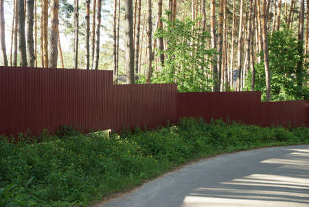 a long red metal fence outside in green grass by a gray asphalt road