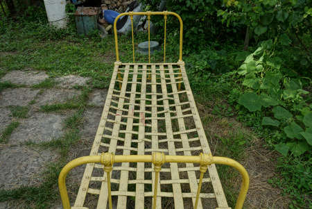 retro yellow iron bed stands on gray ground and green grass in a summer garden 写真素材