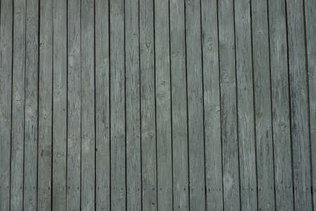 wooden texture from gray thin boards in the fence wall on the street