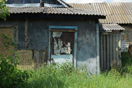 an old shabby door on a gray wall of an abandoned rural house overgrown with green grass and vegetation