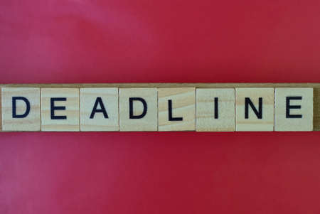 text the word deadline from gray wooden small letters with black font on an red table