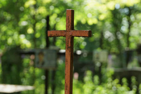 one old brown iron cross in a spider web on a green background in a cemetery 写真素材