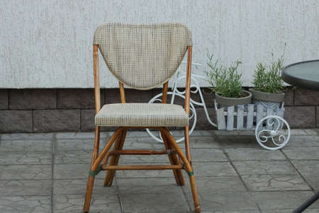 one brown wooden chair with a soft seat stands on a gray sidewalk outside in a summer cafe Stockfoto