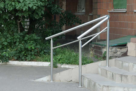 white metal handrails at the gray steps on the threshold of the building on the street