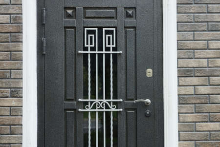 black iron closed door with a gray wrought pattern on the brick wall of the house