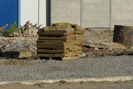 a pile of brown pieces of insulation stands on gray rubble on the street near the stone wall of the fence