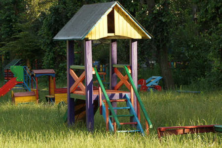 colored wooden house with a ladder on the playground in the green grass Stockfoto