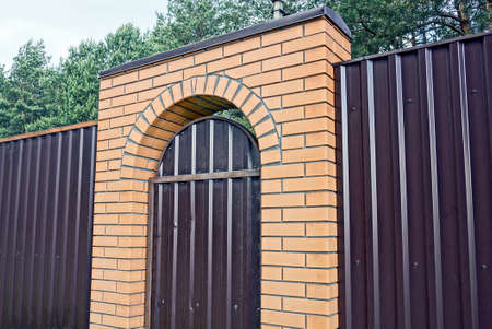 brown metal fence wall with closed door and brick arch on the street Stockfoto