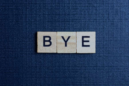 text on word bye from gray wooden letters on a black background