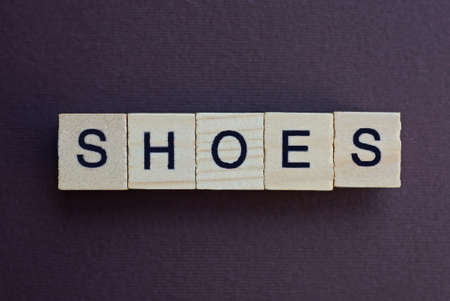 gray word shoes made of wooden square letters on brown background Stockfoto