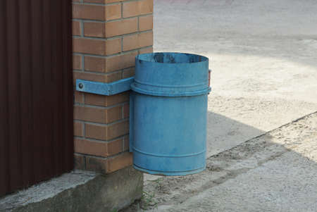 one blue iron urn hanging on a brown brick wall outside Stockfoto