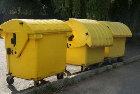 three yellow closed trash cans stand on the gray asphalt outside Stockfoto