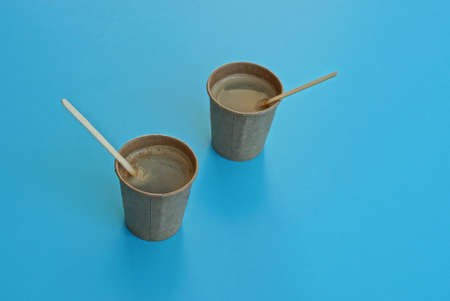 two brown paper cups full of coffee stand on a blue table