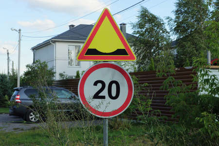 two road signs a speed bump and a speed limit on the street by the road in green vegetation Stockfoto