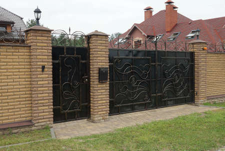 one closed black metal gates a forged pattern and part of a brick brown fence